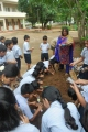 Co ordinator Ma'am Perpetua instructing children about the composition of the soil
