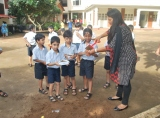 The teacher giving the children 3 parts soil and 1 part compost for seed germination